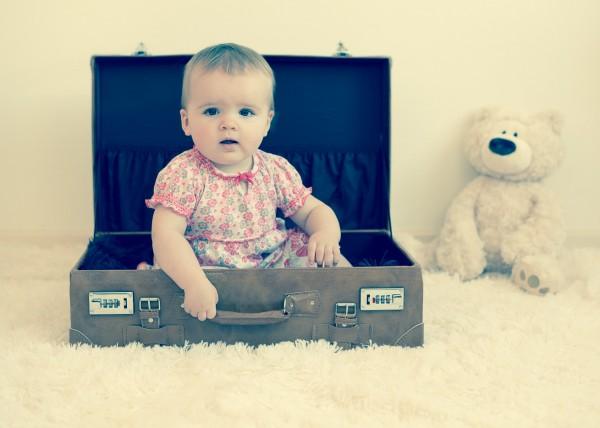 Enfant fille assise dans une valise avec un ourson peluche